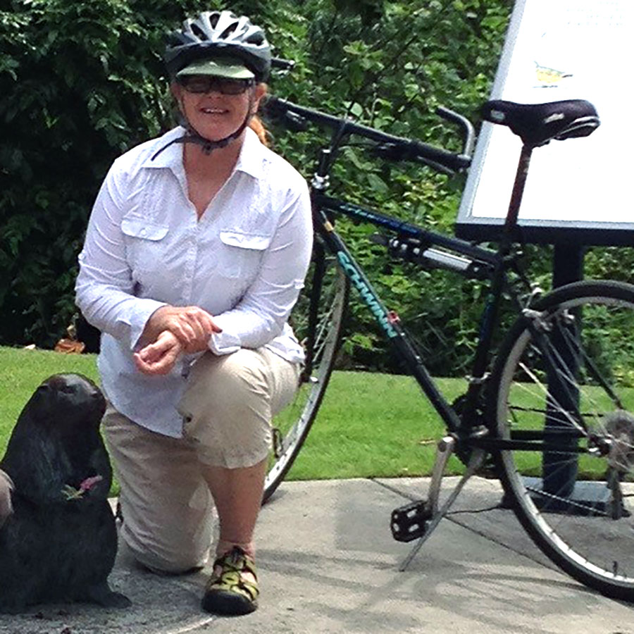 Deb Scott kneeling next to the bronze beaver sculpture on the Willamette Greenway